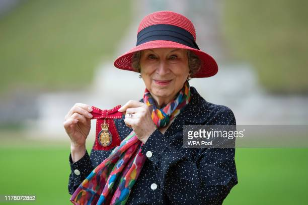 Dr Margaret Atwood poses with her award after she was made a Companion of Honour by Queen Elizabeth II following an investiture ceremony at...