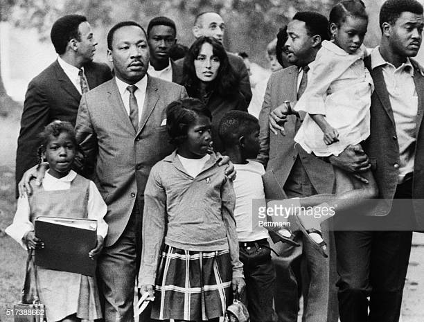Dr Martin Luther King is shown leading a group of black children to their newly integrated school in Grenada Mississippi escorted by folk singer Joan...