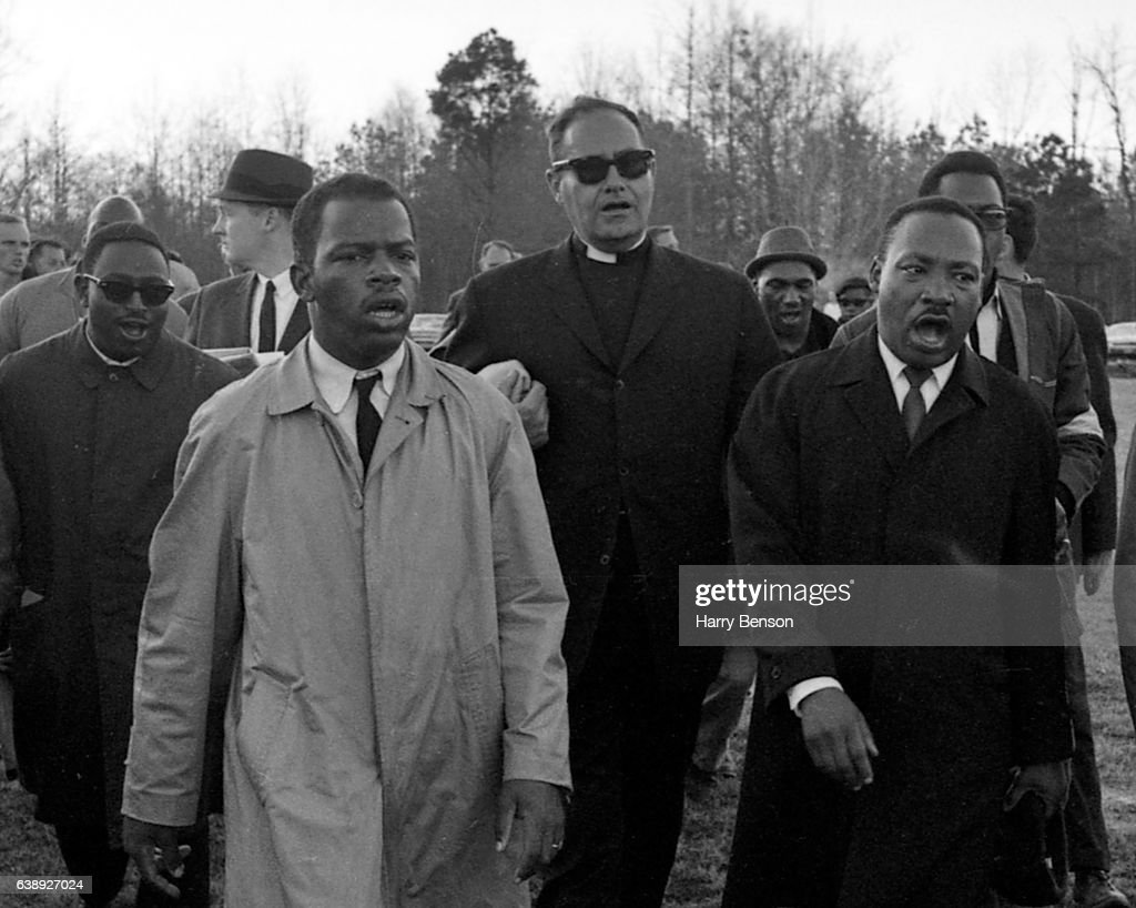 "Dr. Martin Luther King, Jr. and Civil Rights Activist and U.S. Congressman John Lewis in light raincoat singing ""We Shall Overcome"" as they marched in Mississippi on the James Meredith March Against Fear in 1966 in Mississippi."