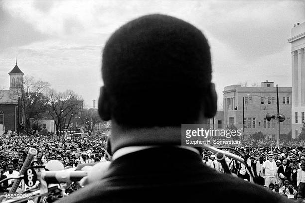 Dr. Martin Luther King, Jr. Seen close from the rear, speaking to 25,000 civil rights marchers in front of the Alabama state capital building, at the...