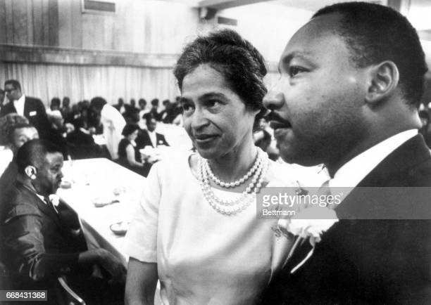 Dr Martin Luther King stands with Rosa Parks at dinner given in her honor during Southern Christian Leadership Conference convention held here 8/10...