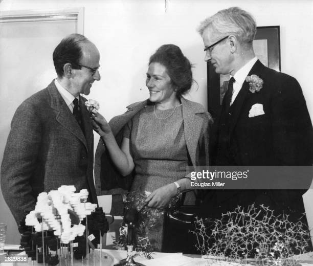Dr Max Ferdinand Perutz receives a carnation from his wife Gisala watched by his colleague Cowderey Kendrew with whom he shared Nobel Prize for...
