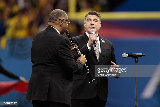 Dr Michael White and actor Bryan Batt perform the National ANthem prior to the Michigan Wolverines playing against the Virginia Tech Hokies during...