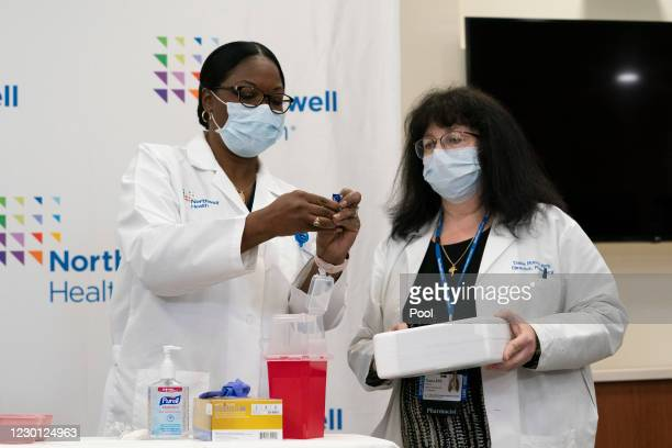 Dr. Michelle Chester, left, holds a vial of the COVID-19 vaccine after it was handed to her by pharmacy director Dana Rucco at Long Island Jewish...