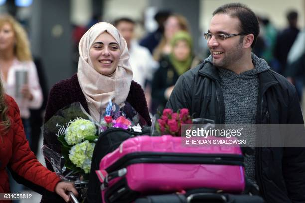 Dr Muhamad Alhaj Moustafa a Syrian citizen walks with his wife Nabil Alhaffar also a Syrian citizen after she returned from a trip to Doha but was...