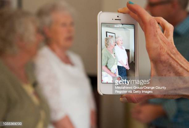 Dr Nancy Segal of Cal State Fullerton uses her cell phone video camera to record the reunion of twin sisters Ann Hunt left of Aldershot England and...