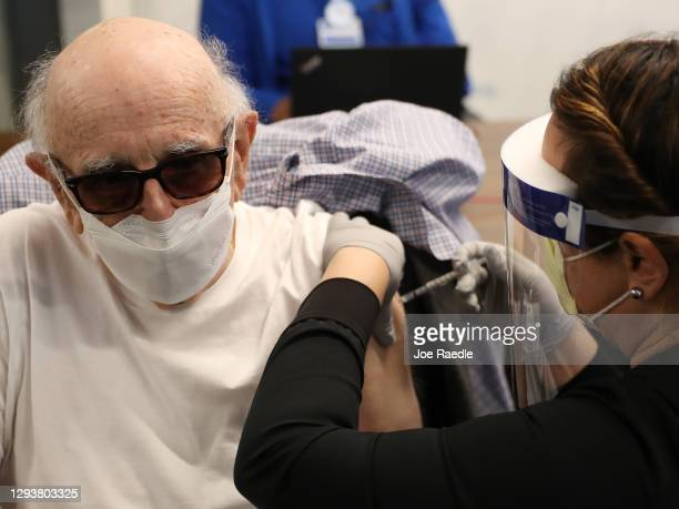 Dr. Norman G. Einspruch receives a Pfizer-BioNtech COVID-19 vaccine from Susana Flores Villamil, RN from Jackson Health System, at the Jackson...