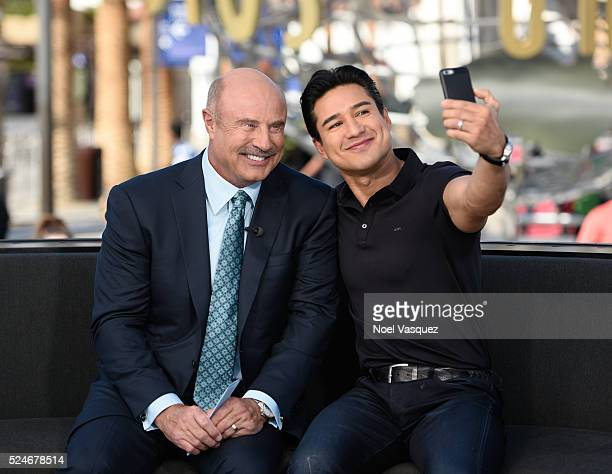 Dr Phil takes a selfie with Mario Lopez at 'Extra' at Universal Studios Hollywood on April 26 2016 in Universal City California