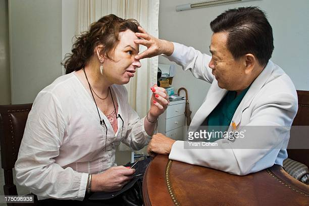 Dr. Preecha Tiewtranon inspects the face of Mandy, one his patients, after performing cosmetic surgery at the Bangkok Nursing Home hospital in...