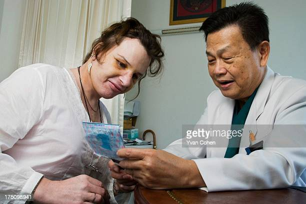 Dr Preecha Tiewtranon inspects the face of Mandy one his patients after performing cosmetic surgery at the Bangkok Nursing Home hospital in...