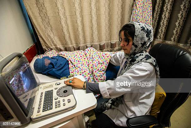 Dr Rayhana Safi makes ultrasound scanning of woman in burka in Central Hospital of Afghan Red Crescent Society Kabul Afghanistan