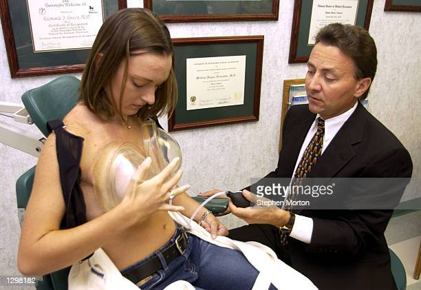 Dr Richard Greco instructs Elizabeth Goolsby on the proper usage of the Brava Breast Enhancement and Shaping System in his office August 7 2002 in...