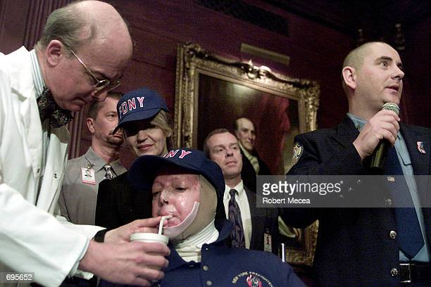 Dr Roger Yurt holds water for Elaine Duch a burn victim from the World trade Center as FDNY EMT Paul Adams first on the scene to treat Duch speaks to...