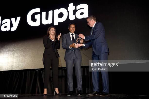 Dr Sanjay Gupta accepts the Bob and Leila Macauley Humanitarian Spirit Award from Erica Hill and Michael J Nyenhuis onstage at the 2019 Americares...