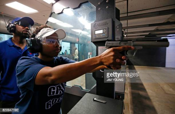Dr Shandrea Boyd shoots at a target as instructor Will Smith looks on during her concealed carry certification test at the Eagle Sports gun range in...