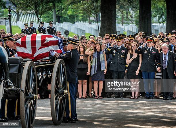Dr. Susan Myers, center, salutes her late husband as his casket is removed from the caisson during the burial service for U.S. Army Maj. Gen. Harold...