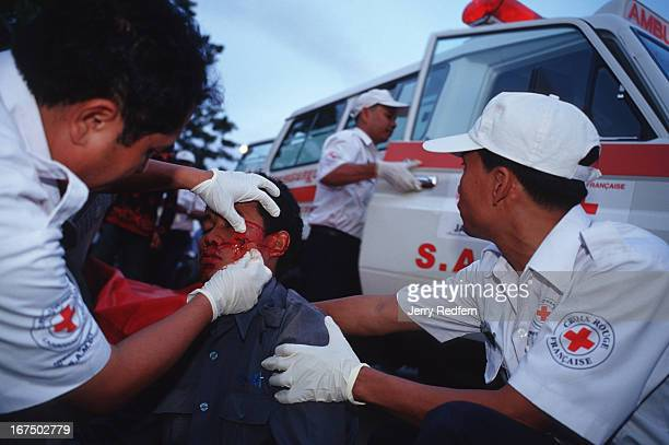 Dr Svay Kamol left head of SAMU examines the bloody wound of a man who was hit by a passing car while riding a bicycle The man a worker for the...