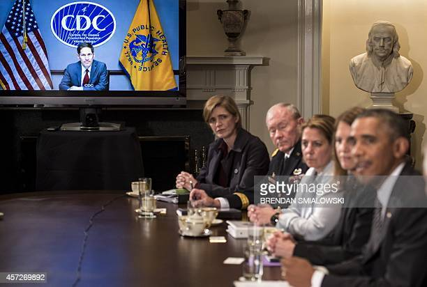Dr Thomas Frieden Director of the Centers for Disease Control and Prevention is seen listening on TV as US President Barack Obama makes a statement...