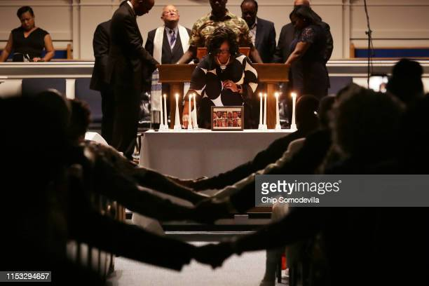 Dr Veronica Coleman of New Jerusalem Ministries lights 12 candles one for each shooting victim as people hold hands across the asile during a...
