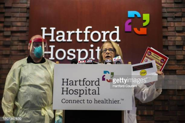 Dr Virginia Bieluch chief of infectious diseases of The Hospital of Central Connecticut holds up precaution signs to be placed outside of patients'...