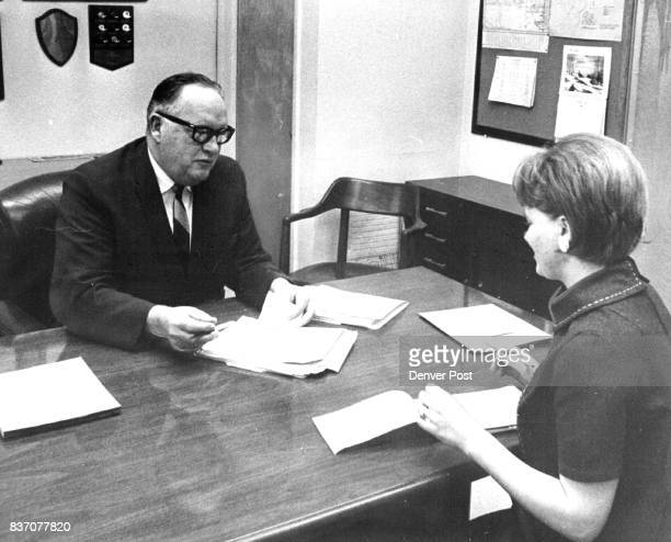 Dr. W. Del Walker, superintendent of the Jefferson County School District, gives instructions on answering a part of a morning's mail to Mrs. Linda...