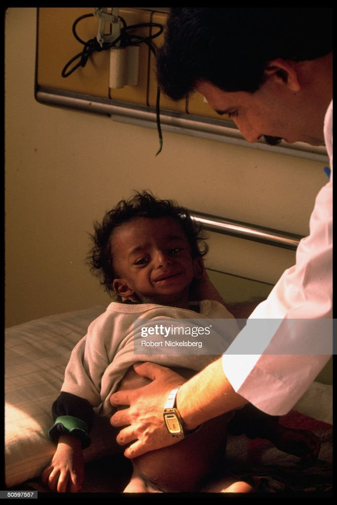 Dr. w. hand on child's swollen belly, at : News Photo