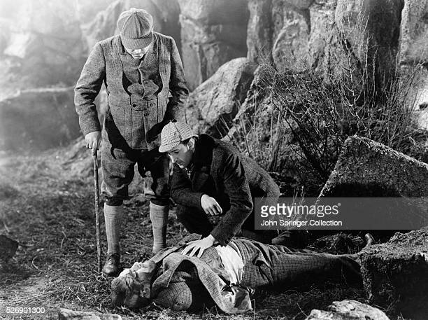 Dr. Watson looks on while Sherlock Holmes kneels over the dead body of Sir Henry Baskerville on the moor.