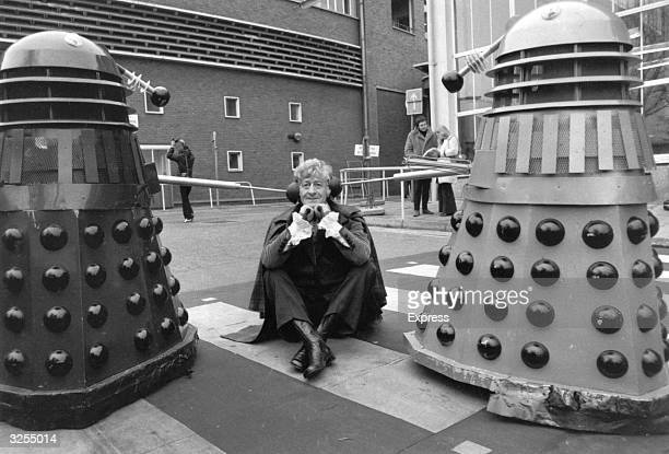 Dr Who played by Jon Pertwee sits in the car park of the BBC guarded by two Daleks robotic creatures from the popular tv series