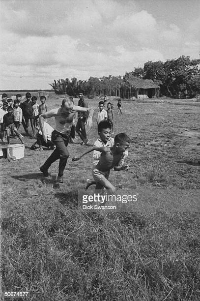 Dr William E Owen playing with Vietnamese children
