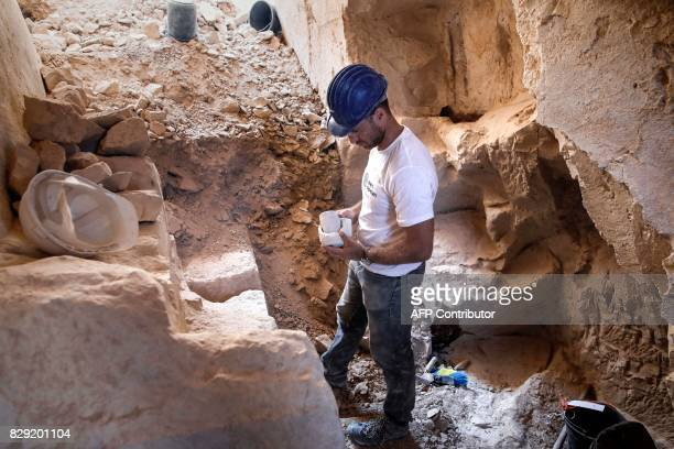 Dr Yonatan Adler director of excavations at a site dating to the Roman period inspects chalkstone mugs and cores uncovered twomonths prior in the...