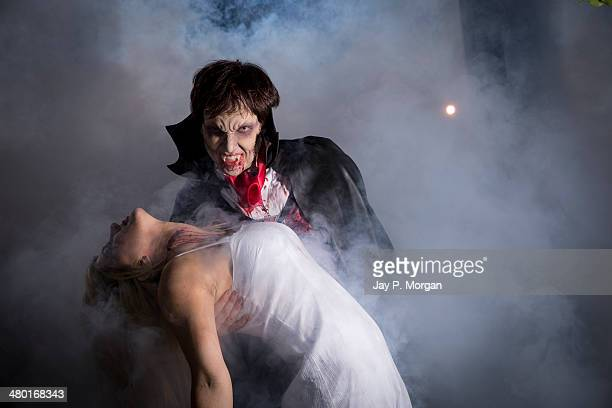 dracula holding an unconscious girl - count dracula stock photos and pictures