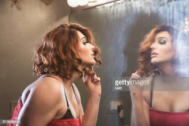 drag queen admiring reflection in mirror - transvestite stock photos and pictures