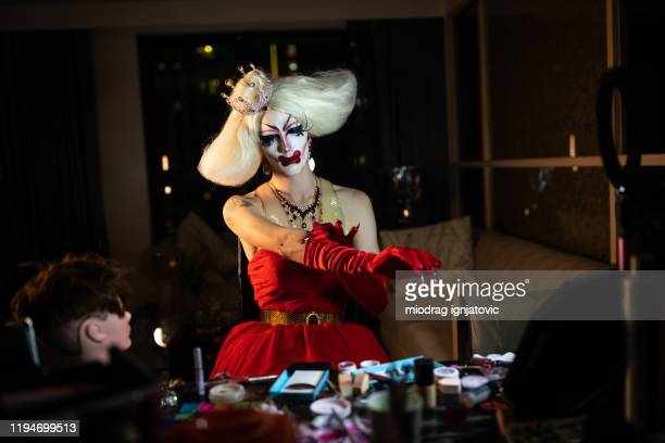 drag queen vestirsi, indossare guanti rossi in una stanza buia - drag queen foto e immagini stock