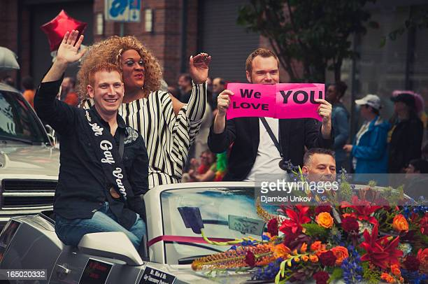Drag queen is accompanied by several men as they waive to the crowd from a convertible during the Portland Gay Pride Parade. A man holds a sign read...