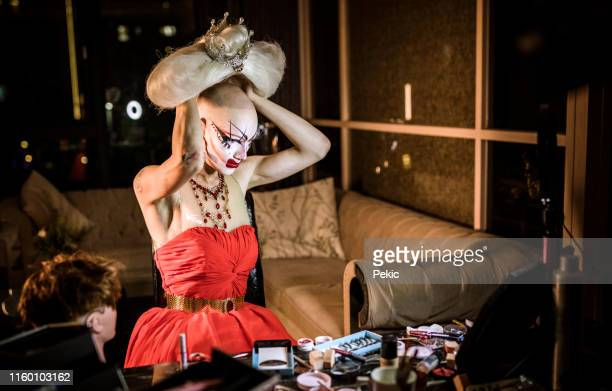 drag queen putting blond wig - burlesque stock pictures, royalty-free photos & images
