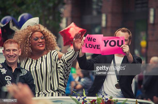 Drag queen rides in a convertible accompanied by escorts as they wave to the crowd and hold signs with messages of love during the Portland Gay Pride...