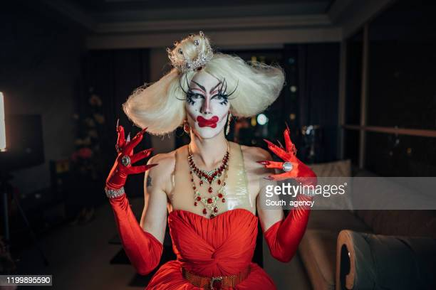drag queen sitting in dark apartment - gender fluid stock pictures, royalty-free photos & images