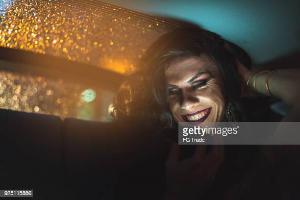 drag queen using mobile at car - transvestite stock photos and pictures