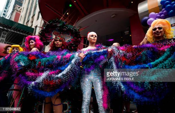 Drag queens hold a feather Boa piled on the ground during an attempt for a Guinness World Records Title for Longest Feather Boa at 12 Miles in...