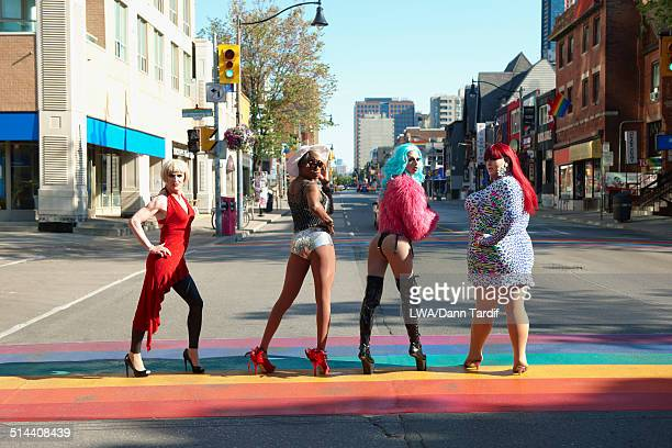 drag queens posing on rainbow pavement on city street, toronto, ontario, canada - transvestite stock photos and pictures