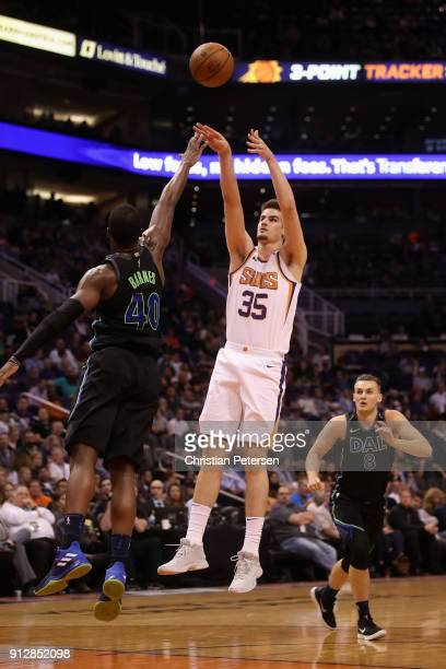 Dragan Bender of the Phoenix Suns attempts a shot over Harrison Barnes of the Dallas Mavericks during the second half of the NBA game at Talking...