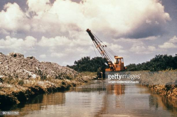 A dragline excavator clearing debris from a drainage canal to prevent the influx of vectorborne diseases and flood damage 1976 Image courtesy CDC