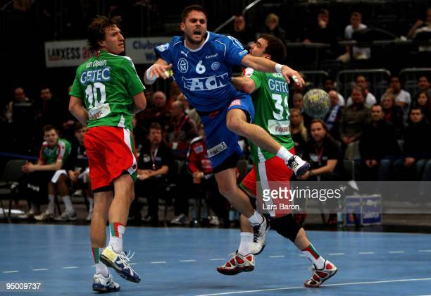 Drago Vukovic of Gummersbach is challenged by Fabian van Olphen and Bartosz Jurecki of Magdeburg during the Toyota Handball Bundesliga match between...