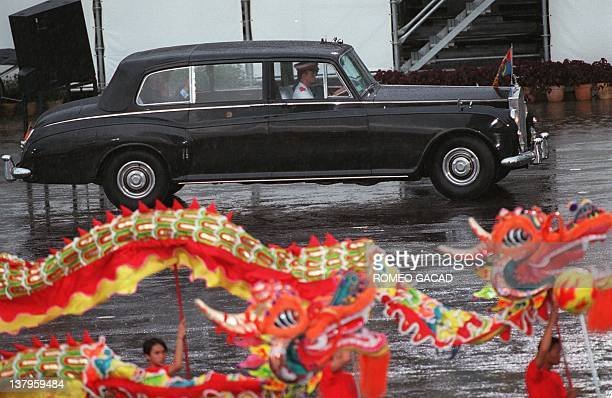 A dragon dance is performed as the official car for Chris Patten and Prince Charles departure passesby following the farewell parade at the former...