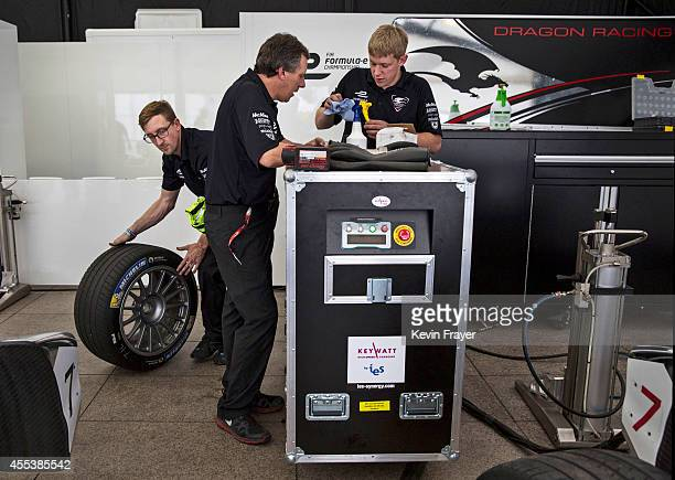 Dragon Racing car techs set up charging equipment for an electric car before the inaugral FIA Formula E Bejing ePrix Championship on September 13...