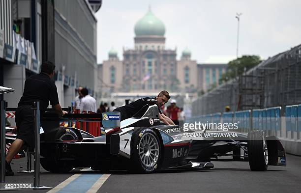 Dragon Racing FormulaE teamcrew push a car in the pitlane at the FormulaE race venue in Putrajaya on November 21 2014 Malaysia will host the second...