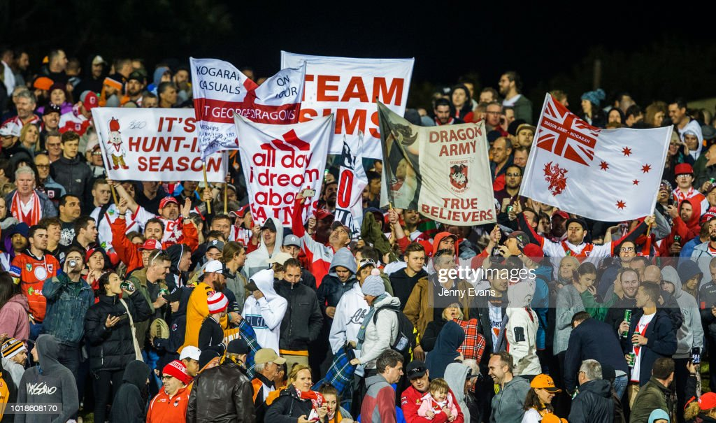 Dragon's fans cheer and hold up banners during the round 23 NRL match between the Wests Tigers and the St George Illawarra Dragons at Leichhardt Oval on August 18, 2018 in Sydney, Australia.