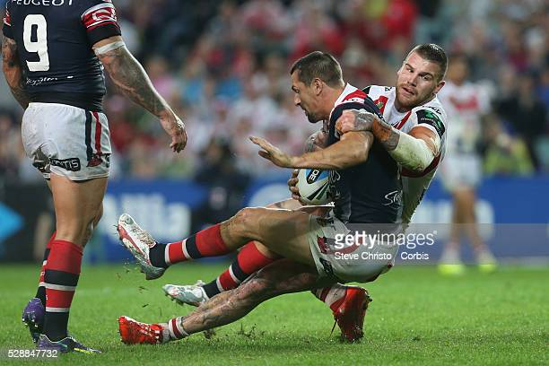 Dragons Josh Dugan wrestles Roosters Mitchell Pearce to the ground in this tackle during their ANZAC day clash at Allianz Stadium. Sydney, Australia....