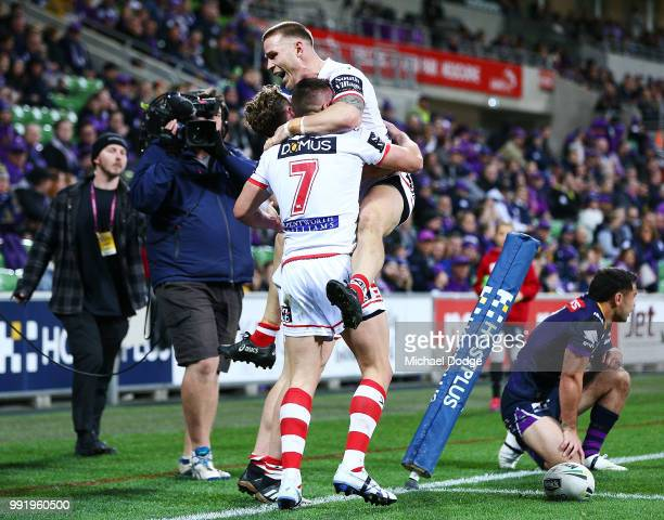 Dragons players celebrate after Kurt Mann of the Dragons scores a try past Jahrome Hughes of the Storm during the round 17 NRL match between the...