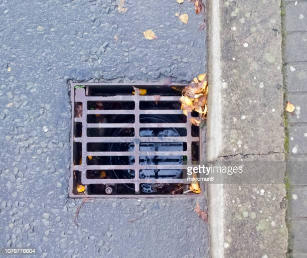 drain in an urban street, gutter at roadside - kerb stock pictures, royalty-free photos & images